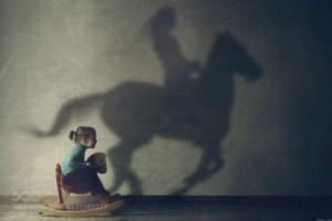 o2q5ocwhky-bimba-sul-cavallo-a-dondolo-proietta-ombra-di-donna-a-cavallo-l-importante-e-continuare_a